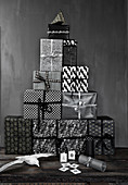 Pile of gifts wrapped in monochrome paper and seagull figurine on wooden table