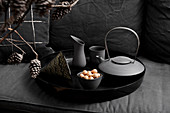 Teapot and containers on black tray
