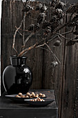Branch of larch cones in black vase
