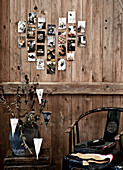 Old photos arranged in love-heart on rustic board wall above chair and side table