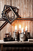 Lit candles on wooden bench below old picture frames on rustic board wall
