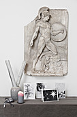 Christmas cards on console table below antique Greek relief on wall