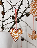 Decorated gingerbread shapes hanging from branch