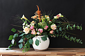 Bouquet of roses, eucalyptus, chrysanthemums, amaranth, carnations, pink pepper, calla lilies and grasses