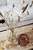 Vase of dried flowers on coffee table with wooden top