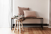 Cushions and fur rug on bench and Christmas decorations on wooden stool