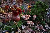 Woodland arrangement of fungi, moss, animal figurines and vase of chrysanthemums and pyracantha berries