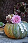 Dahlia and hydrangea flowers with lace ribbon on top of pumpkin