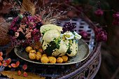 Autumn arrangement of squash, crabapples, rose and scabious