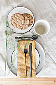 Place setting decorated with grasses on pale tablecloth