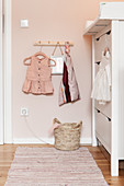 Baby clothes on coat rack next to changing unit