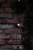 Lichterkette vor Ziegelwand auf der Terrasse