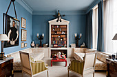 Wedgewood blue sitting room with winged victory lights, pedimented bookcase, red lacquer low table and Elizabethan portrait