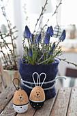 Easter arrangement of grape hyacinths in felt collar and wooden Easter bunnies
