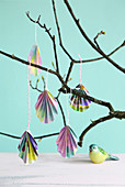 Folded paper Easter eggs hanging from branch