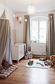 Fabric canopy, cot and play mat in nursery