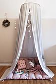 Stoffhimmel, darunter Decke, Kissen und Spielzeug im Kinderzimmer