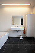 White sink cupboard and bathtub in bathroom with black tiled floor