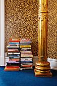 Bücherstapel und goldene Säule vor Tapete mit Leopardenmuster