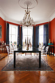 Dining room with red walls and designer chairs