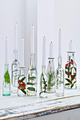 Upcycling idea: leafy branches in bottles filled with water used as decorative candlesticks