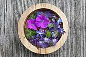 Blüten von Malve, Borretsch und Büschelschön in Holzschale