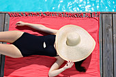 Woman in swimsuit by swimming pool with straw sunhat over face