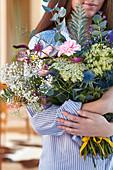 Woman holding bouquet of carnations, gypsophila, wild carrot, veronica, globe thistle, astrantia and eucalyptus