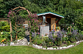 Summer allotment garden with garden house, rose arch with woodland vine 'Avant-Garde' and perennial bed with lavender tied together
