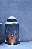 Mit Kerze beleuchteter Buddhakopf im Schnee