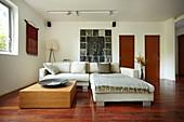Sofagarnitur und niedriger Tisch im Wohnzimmer mit Teakholzboden