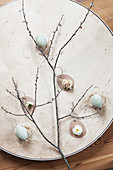 Easter arrangement of branch, Easter eggs, roses, narcissus and waxflower