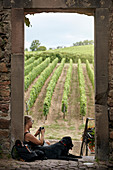 Woman and dog resting, vineyard on background
