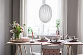 Frühlingsstrauß auf gedecktem Tisch in Puderrosa-Tönen