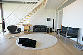 Black leather furniture, round rug and staircase in background of loft apartment