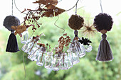 Handmade garland made from miniature glass bottles holding dried grasses and pompoms with tassels