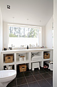 White washstand with shelves below window in bathroom