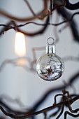 Silver Christmas bauble hanging from branch