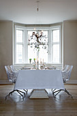 Table set in white for Christmas meal and designer chairs