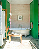 Free-standing bathtub between green walls