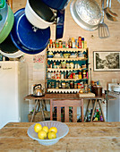 Pans hanging over kitchen table with shelved in background