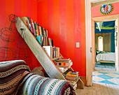 Alte Leiter als Bücherregal im Zimmer mit roten Wänden