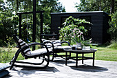 Black chairs and round table on wooden terrace