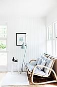 Rattanbank vor Fenster im Zimmer mit weißer Holzverkleidung