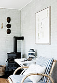 Rattan chair with striped cushion, tray table and cast iron, wood-burning stove