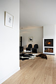 Black classic chairs, coffee table on cowhide tug and dog in front of fireplace in open-plan interior