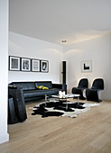 Black classic chairs, leather sofa and coffee table on cowhide rug in living room