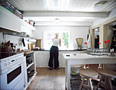 Woman in kitchen-dining room with white cabinets and black worksurfaces