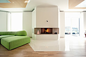 Fireplace and green modular sofa in living room