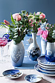 Spring flowers with eucalyptus sprigs in blue-and-white vases